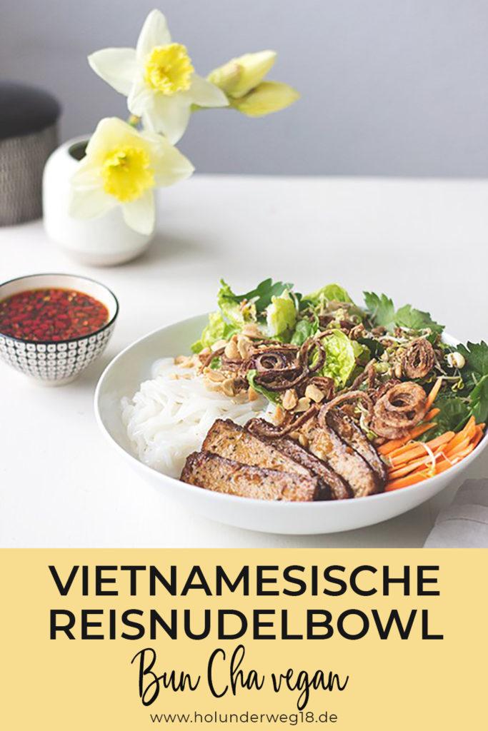 Ein Teller mit geröstetem Tofu, Reisnudeln, Salat, Röstzwiebeln und einer kleinen Schale Chili-Sauce.